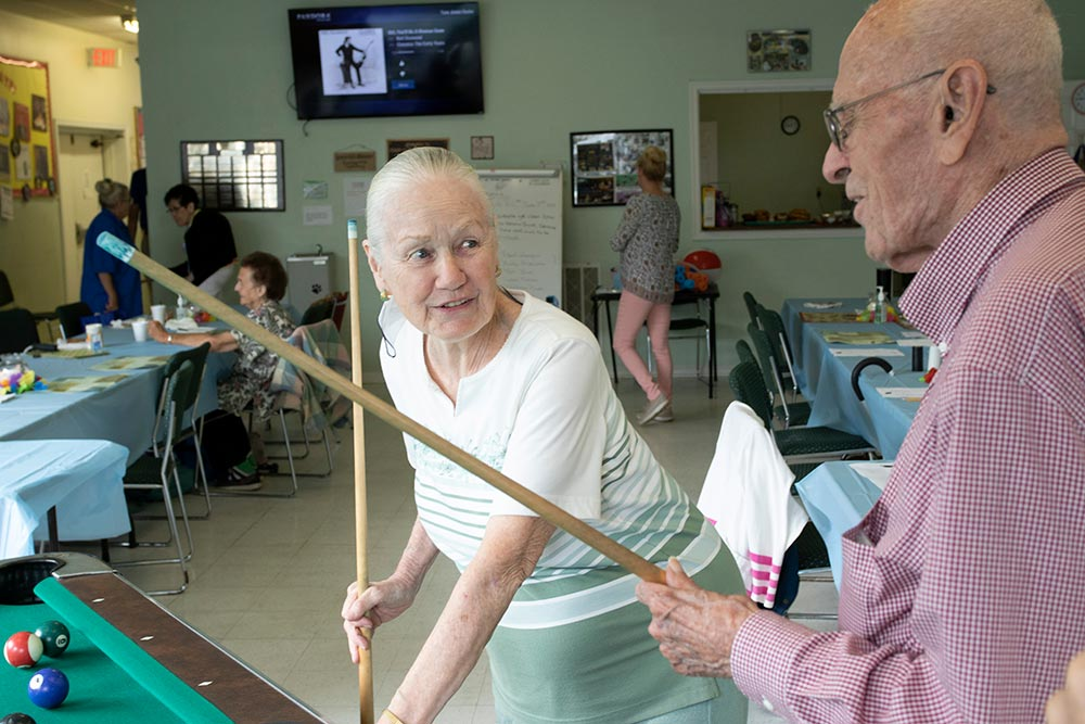 Bay Aging Community Living members playing pool and socializing