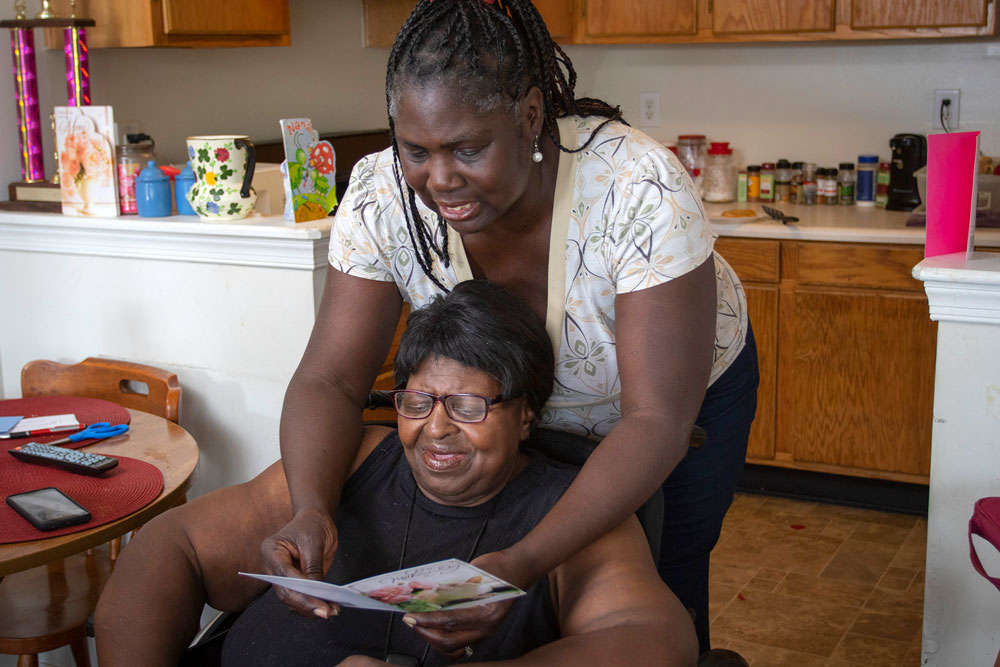 Senior resident being read a card in her home from a woman