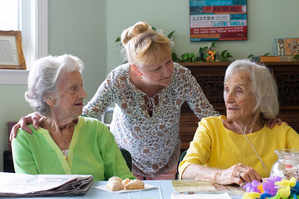 Two senior women being greeted by a Bay Aging staff member