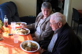 Man and woman having Thanksgiving meal at Adult Day Care Center
