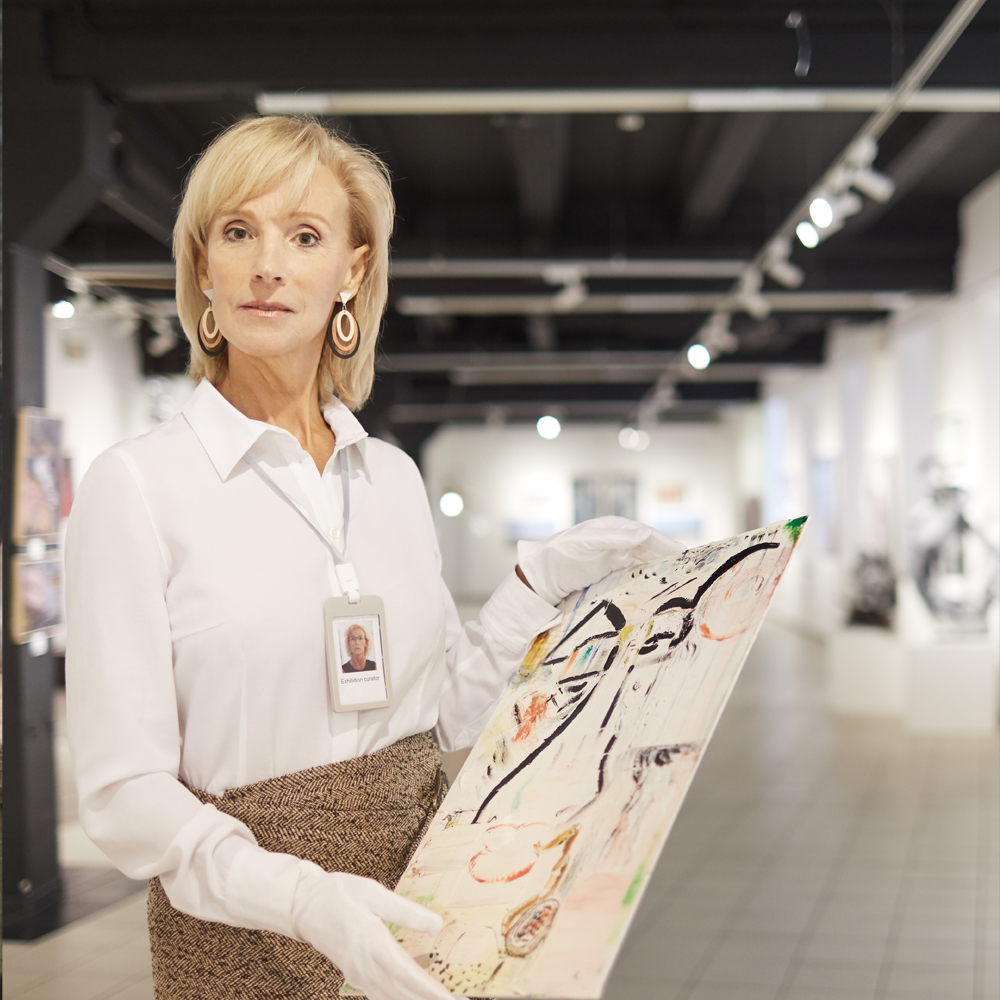 Female art expert holding painting at museum