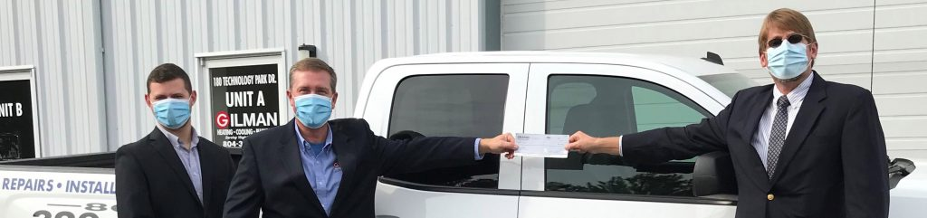 People in front of Truck holding donation check