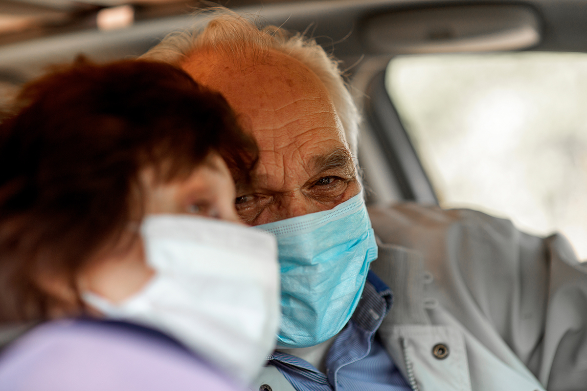 An elderly man in a medical face mask driving a car