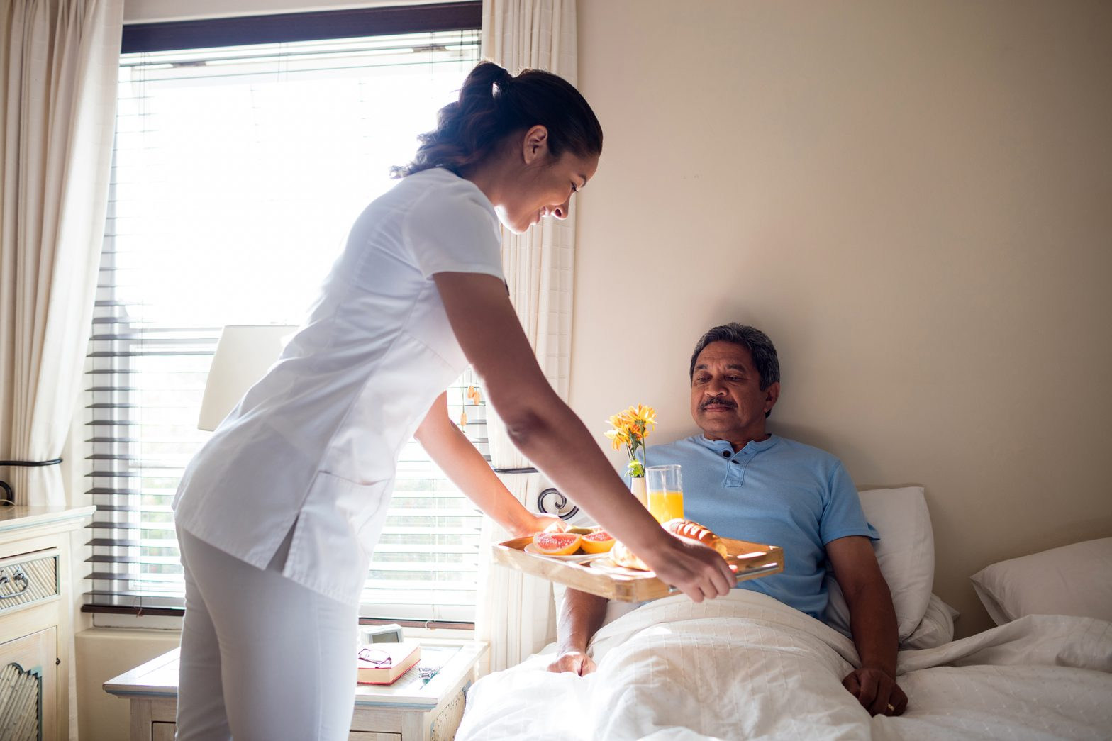 Doctor serving breakfast to senior patient in bedroom