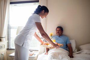 Doctor serving breakfast to senior patient in bedroom